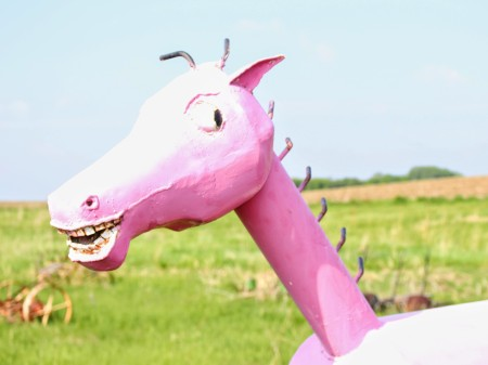 A big, bubble gum pink rocking horse with a mischievous grin.