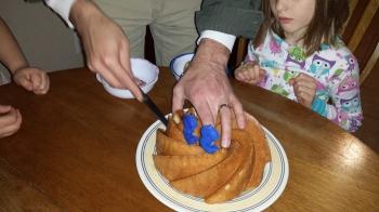 Cutting a slice of birthday cake.