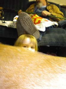 Our youngest daughter peeking over the furry yellow back of Ross the Dog.