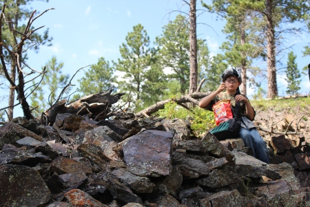 My son enjoying a moment on a pile of stones left over from mining attempts.